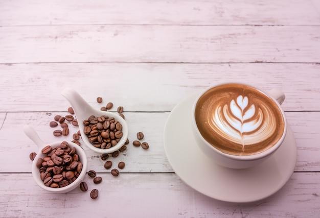 Capuchino caliente con granos de café tostados sobre un fondo de madera y espacio libre