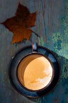 Capuchino con espuma, taza de café azul sobre fondo de madera
