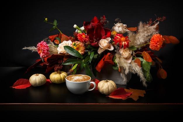 Capuchino y hermosas flores naturaleza muerta. composición de la tienda de flores. taza de café con espuma, manzana, ramo de flores frescas y secas en la mesa de madera negra. arte de floristería y concepto de diseño floral.