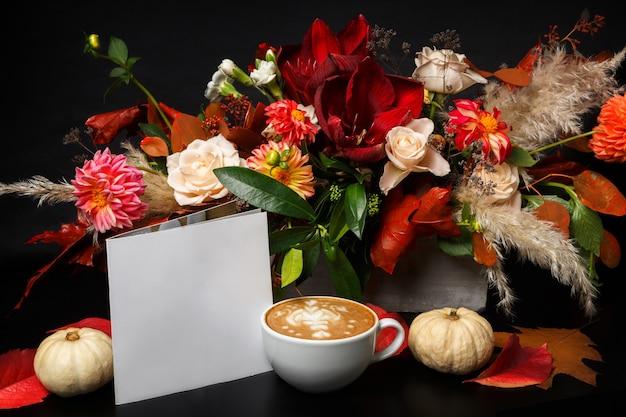 Capuchino y hermosas flores naturaleza muerta. composición de la tienda de flores. taza de café, manzana fresca y bouquet en mesa de madera negra. arte de floristería y concepto de diseño floral.