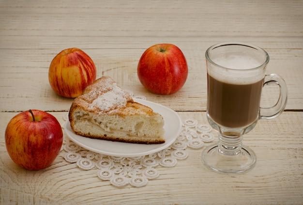 Capuchino, manzanas maduras y tarta de manzana sobre una mesa de madera blanca