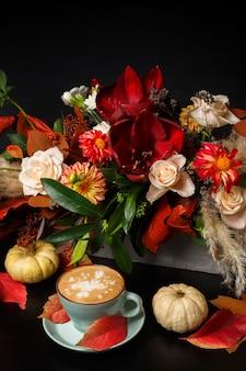 Capuchino y ramo de flores hermosas naturaleza muerta. composición de la tienda de flores. taza de café, calabazas en mesa de madera negra. arte de floristería y concepto de diseño floral.