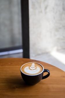 Capuchino sabroso con hermoso arte latte en mesa de madera en el café.