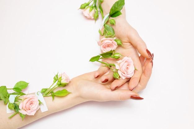 Capullos de rosa en las manos, cuidado de la piel de las manos