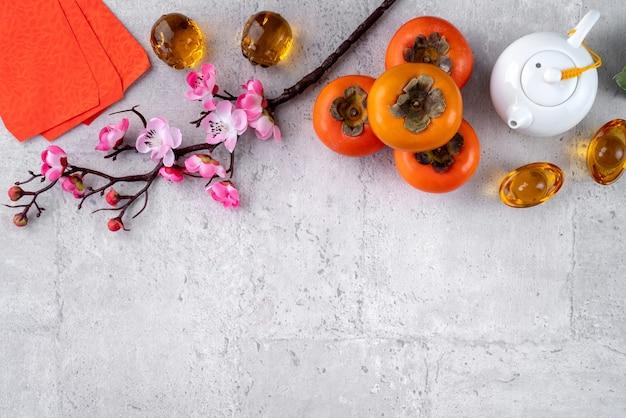 Caquis frescos sobre fondo gris de mesa para el diseño de frutas de año nuevo chino, las palabras en la moneda de oro significan el nombre de la dinastía que hizo.