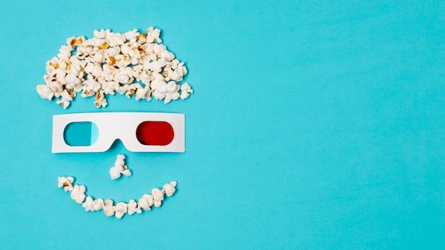 Cara antropomorfa sonriente hecha con palomitas de maíz y gafas 3d sobre el texto de la hora del cine