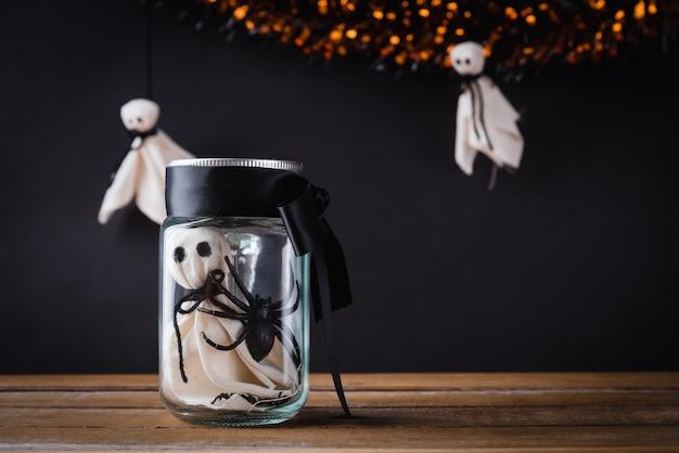 La cara aterradora del fantasma blanco y la araña negra en un tarro de cristal en la mesa de madera