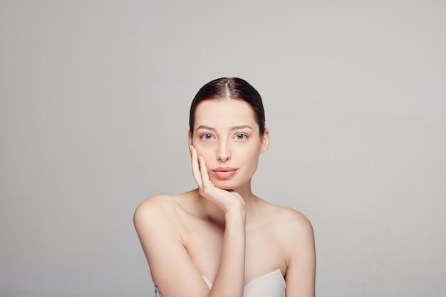 Cara de belleza hermosa mujer con maquillaje natural toca su propia cara con la mano derecha.