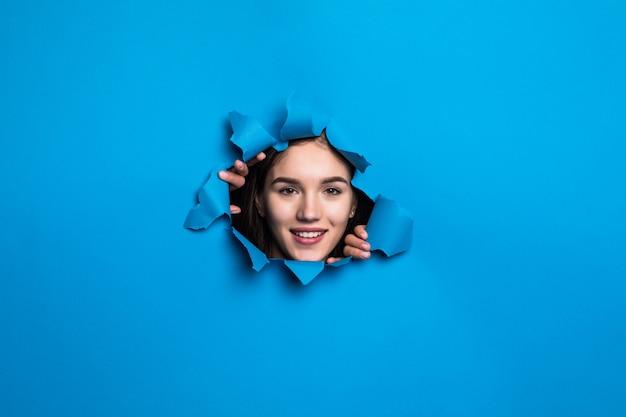 Cara bonita joven mirando a través del agujero azul en la pared de papel.