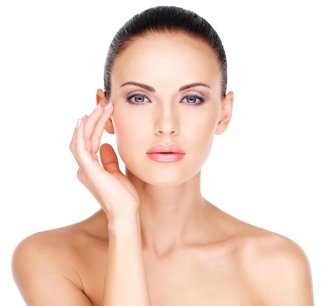 Cara bonita de una mujer hermosa que toca la piel cerca de los ojos - aislado en blanco