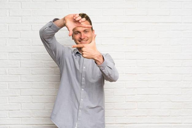 Cara de concentración de la pared de ladrillo blanca del hombre rubio. símbolo de encuadre