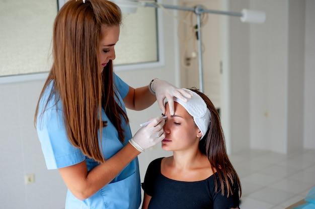 Cara cosmetología cirugía plástica belleza concepto joven morena mujer recibiendo inyección de ácido hialurónico por jeringa