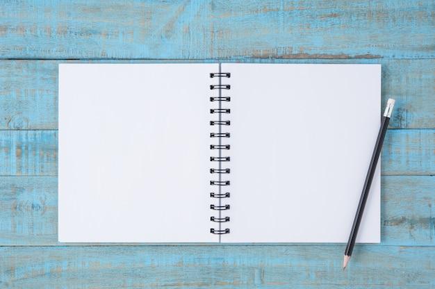 Cara de cuaderno y lápiz sobre la mesa de madera azul vintage