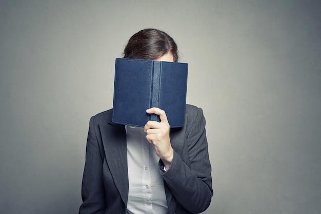 Cara de la cubierta de la mujer de negocios con el diario del organizador