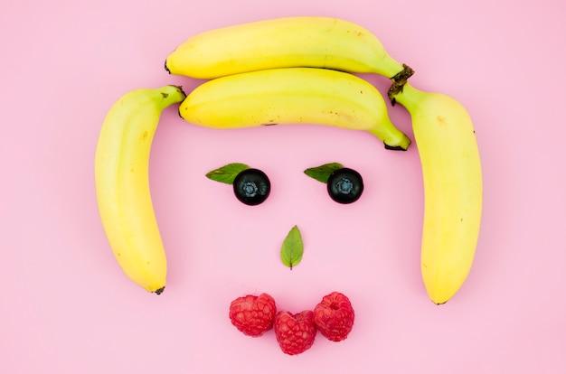 Cara divertida hecha de frutas y bayas en superficie clara.