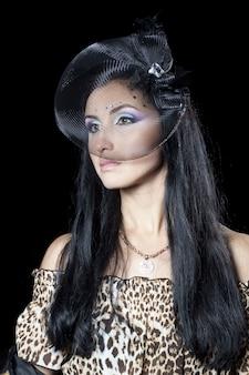 La cara con estilo hermosa de la mujer joven en el velo aislada en negro.