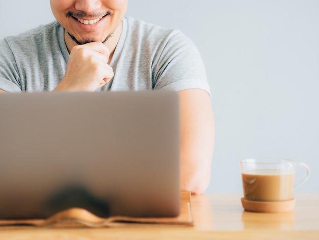 Cara feliz hombre trabajo en su computadora portátil.