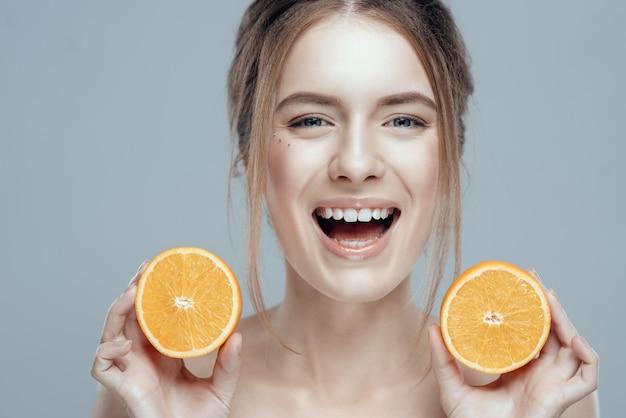 Cara feliz con la naranja jugosa en fondo gris.