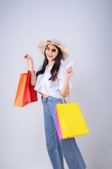 Cara feliz y sonrisa de la mujer asiática joven que sostiene un color de la bolsa de compras y una factura en el fondo blanco.