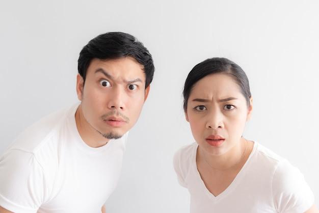La cara graciosa de los amantes de la pareja en duda ante algo increíble que están mirando