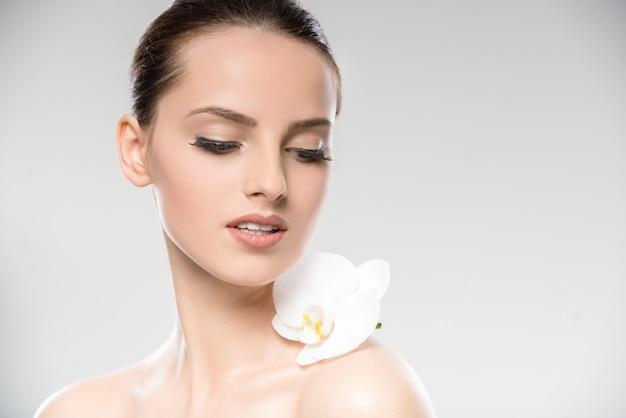 Cara hermosa de la mujer joven con una flor blanca de la orquídea.