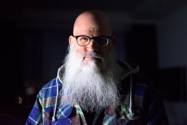 Cara de hombre hipster barbudo calvo maduro con anteojos en casa en la oscuridad