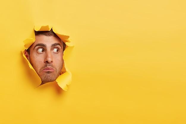 La cara del joven asustado sorprendido mira a un lado a través del agujero de papel amarillo, ve algo impactante, tiene los ojos bien abiertos