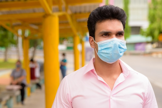 Cara de joven empresario indio con máscara esperando en la parada de autobús