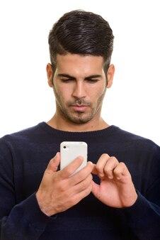 Cara de joven guapo persa mediante teléfono móvil