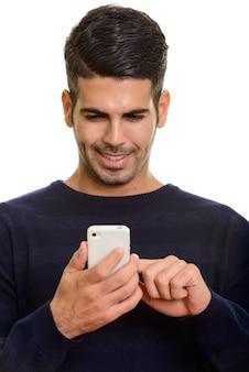 Cara de joven persa feliz sonriendo y mediante teléfono móvil