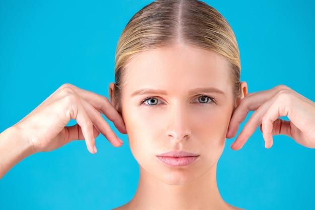 Cara limpia de hermosa mujer joven apuntando a su oído