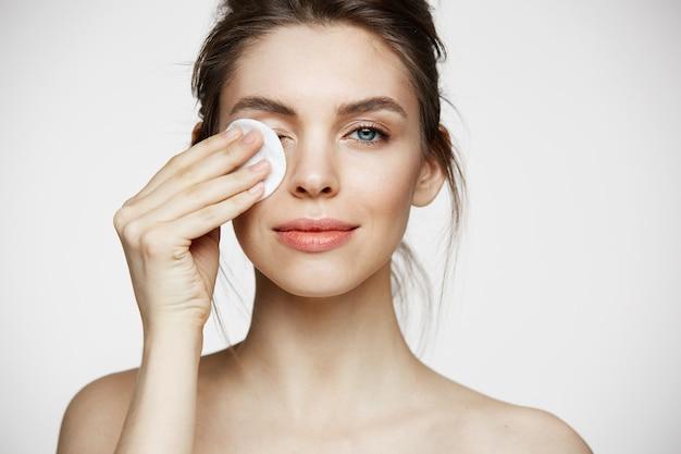 Cara de limpieza hermosa chica morena natural hermosa con esponja de algodón sonriendo mirando a cámara sobre fondo blanco. cosmetología y spa.