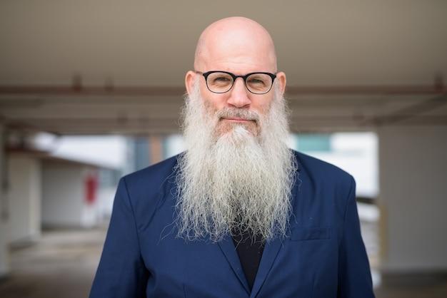 Cara de maduro guapo empresario barbudo calvo en traje con anteojos al aire libre