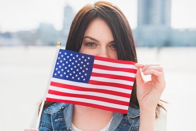 Cara de mujer joven que cubre con bandera americana