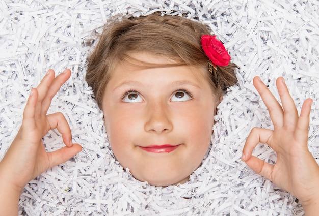 Cara de una niña que emerge de una montaña de papel rasgado mientras hace yoga