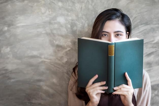 Cara de ocultación de la mujer hermosa detrás del libro verde mientras que mira la cámara.