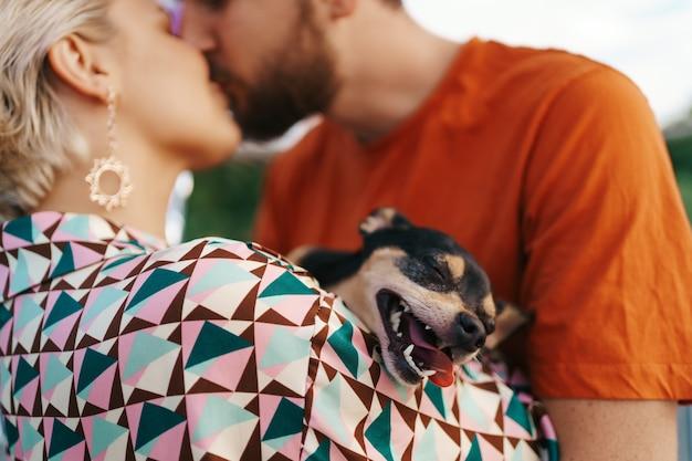Cara de perro sonriente mientras sus seres humanos besándose abrazándolo