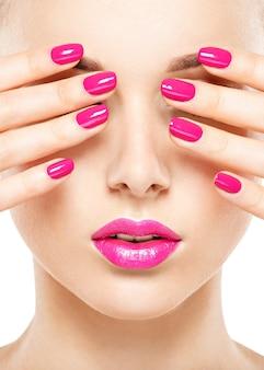 Cara de primer plano de una hermosa niña con labios y uñas de color rosa brillante.