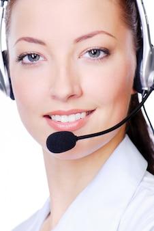 Cara de primer plano de mujer adulta joven en auriculares en blanco