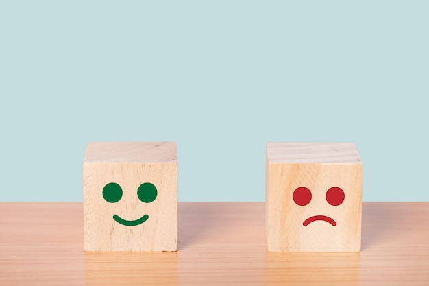 Cara sonriente e icono de cara triste borrosa en el cubo de madera, calificación de servicio al cliente, concepto de encuesta de satisfacción.