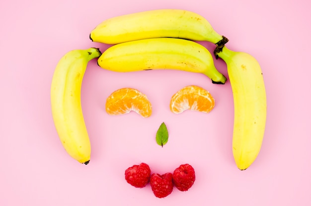 Cara sonriente feliz de la fruta en superficie ligera