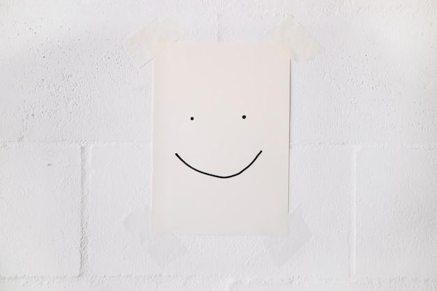Cara sonriente hecha en papel blanco palo en la pared con cinta