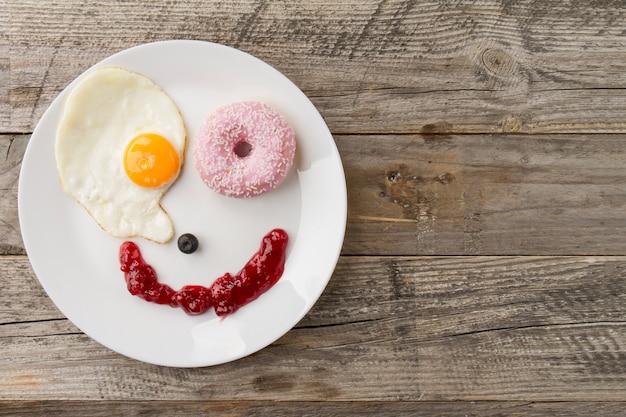 Cara sonriente de huevo frito y rosquilla