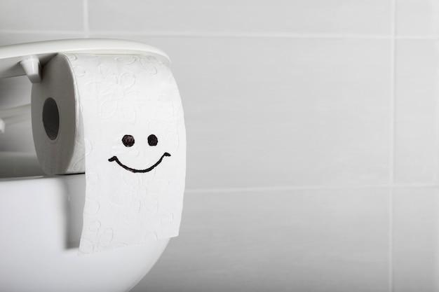 Cara sonriente en rollo de papel higiénico con espacio de copia