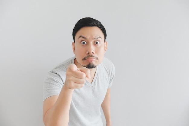 Cara sorprendida del hombre en camiseta gris con el punto de la mano en espacio vacío.