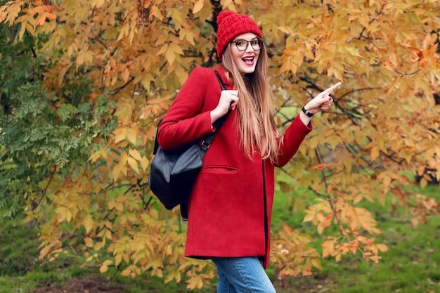 Cara sorprendida parque de otoño señora bastante joven caminando y disfrutando de la naturaleza.