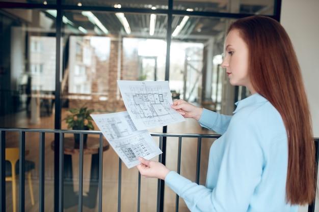 Característica de construcción. adulto joven inteligente buena mujer con pelo largo rojo reflexionando sobre el plan de construcción de pie en el interior frente a una pared de vidrio