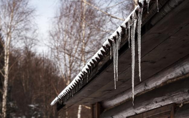 Carámbanos colgando en el techo de la casa de madera