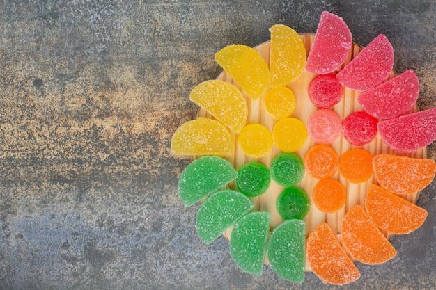 Caramelo dulce de gelatina de colores en placa de madera