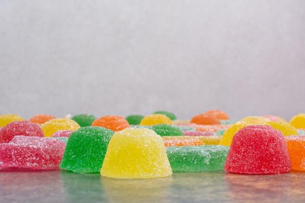 Caramelo dulce de gelatina de colores sobre fondo de mármol